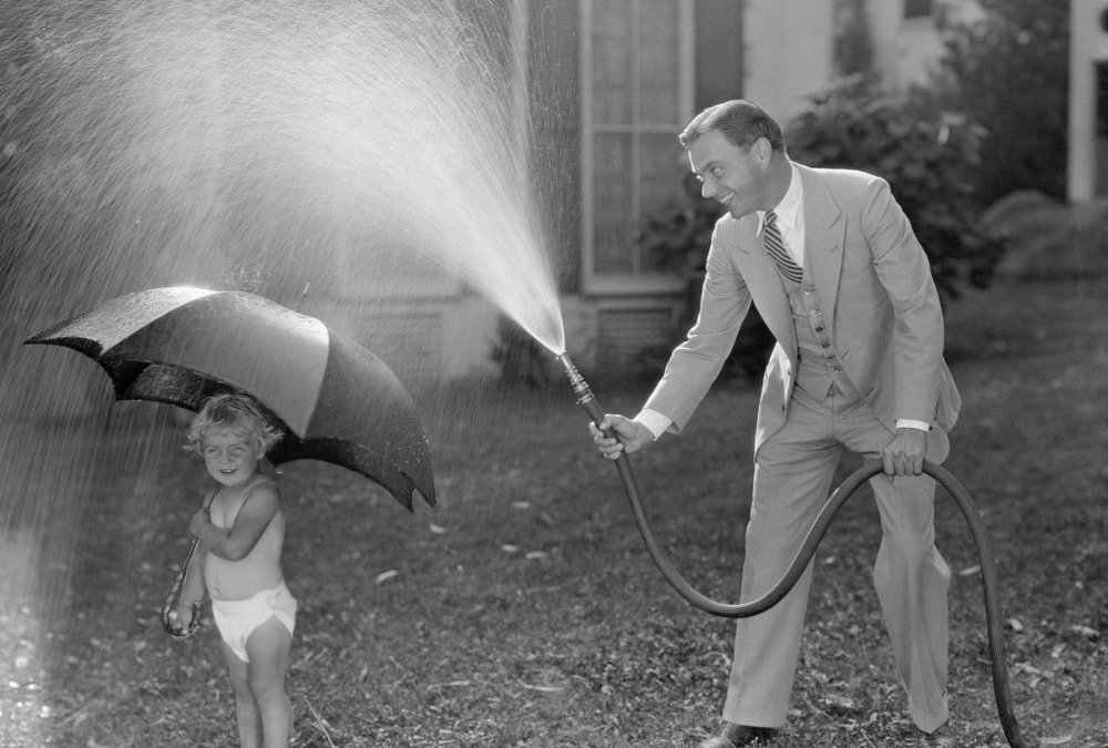 black and white photo of a father in a suit spraying a child with a hose, the child is wearing a diaper and holding an umbrella to block the spray. They both appear to be laughing