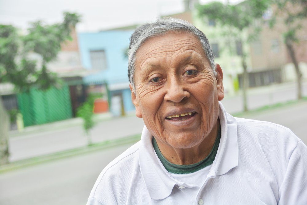 Senior latino standing in an empty street. Portrait with storefronts blurred. Many seniors live independently, but rely on interdependent care and support of family and friends. Social distancing puts them at risk of accidental poisoning, malnutrition, and falling