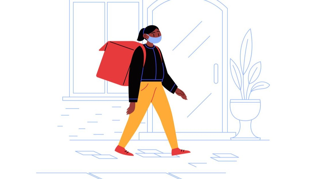 Delivery woman on her way to a client with a thermobag walking down the street wearing medical face mask