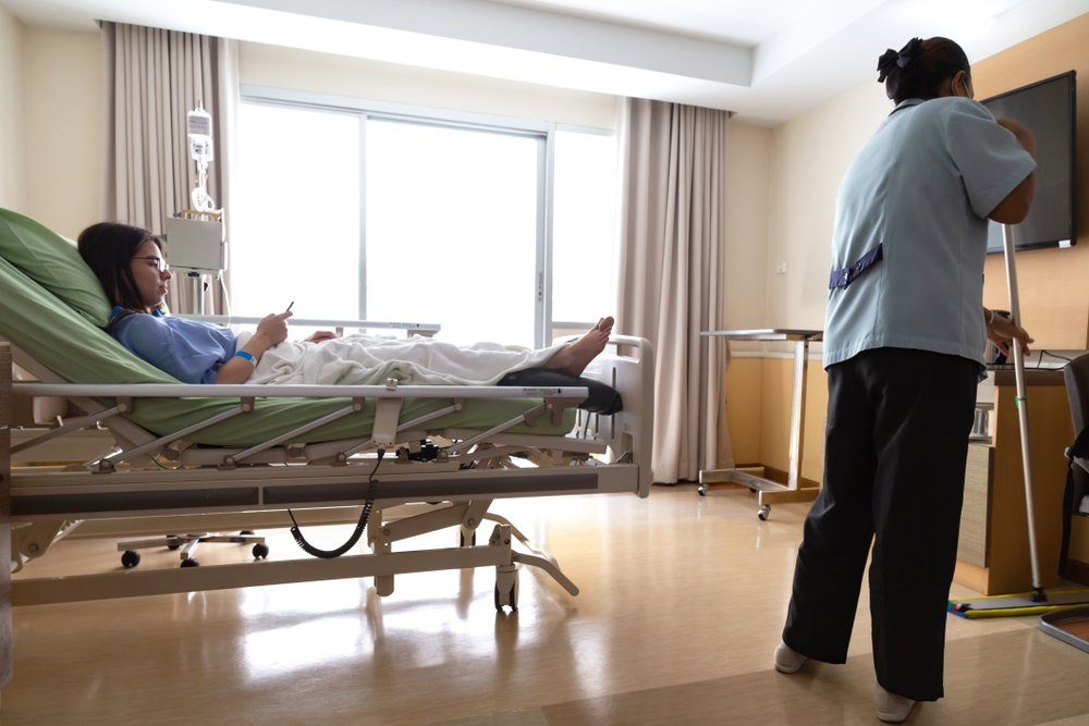 asian hospital room service cleaner woman are cleaning floor with mop in patient room while young patient woman lying in hospital bed and using smart mobile phone while recovering in hospital