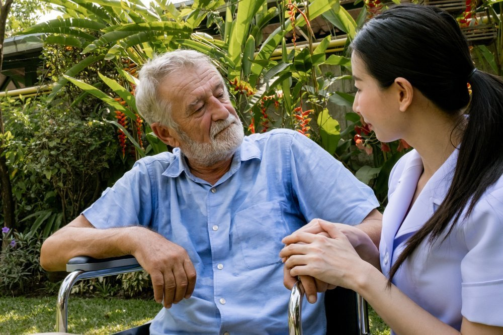senior man happiness sitting on wheelchair with smiling nurse, takes care and discussion and cheer in the garden at nursing home