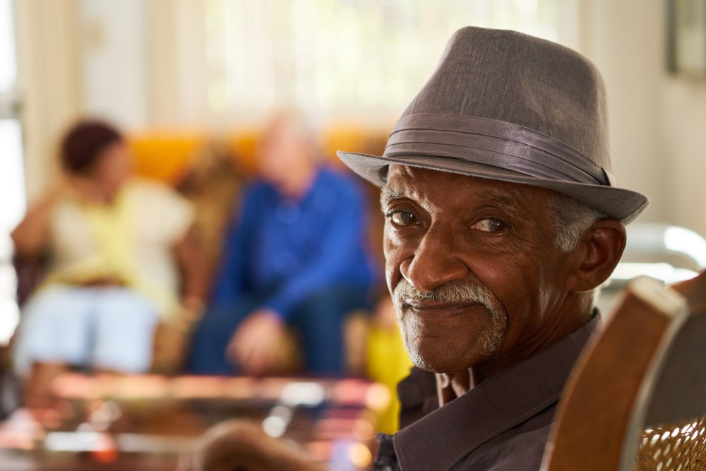 Portrait of elderly black man looking at camera in retirement home, with group of friends in background