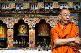 Monk and prayer wheels, Paro, Bhutan