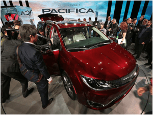 Fiat Chrysler showcased its Pacifica mini van at the North American International Auto Show, seen here being admired from the outside and the interior.