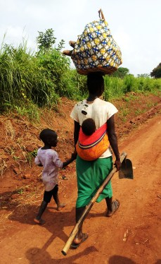 Women in Uganda know how to carrying multiple items. You can't see the water jug on her head in this picture! About an hour away from Gulu.
