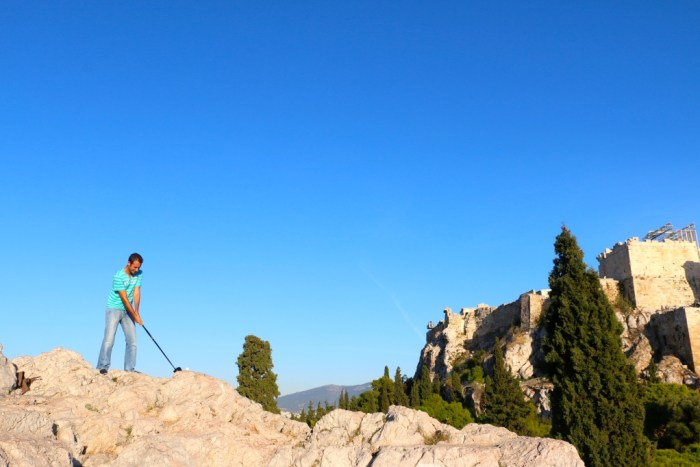 They never said you couldn't golf, while standing on the rocks right off the Acropolis