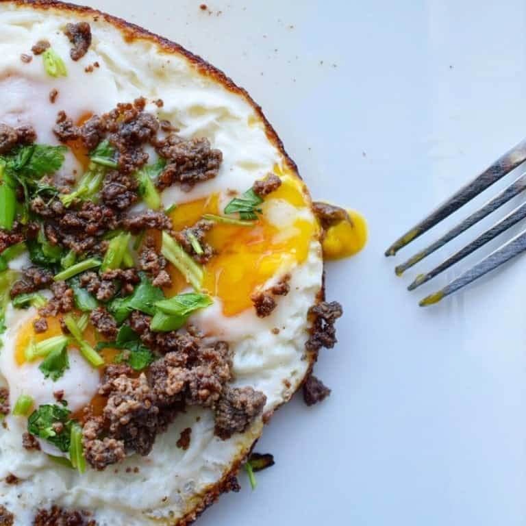 fried eggs topped with roasted lemon crispy beef and green onion