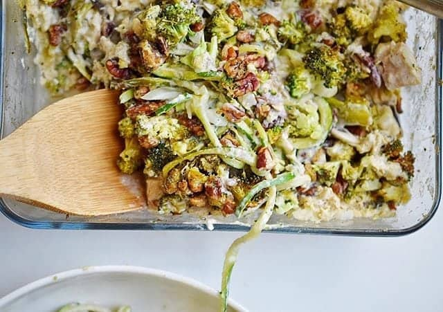 glass casserole dish with zoodles and vegetables and wooden spatula