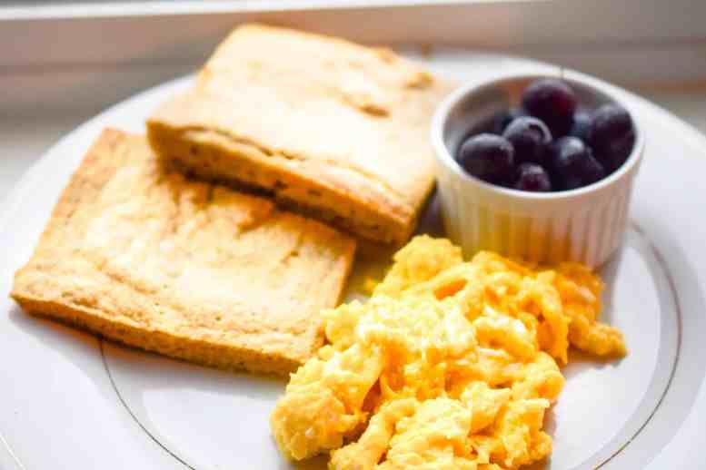 scrambled eggs with toast and berries on white plate