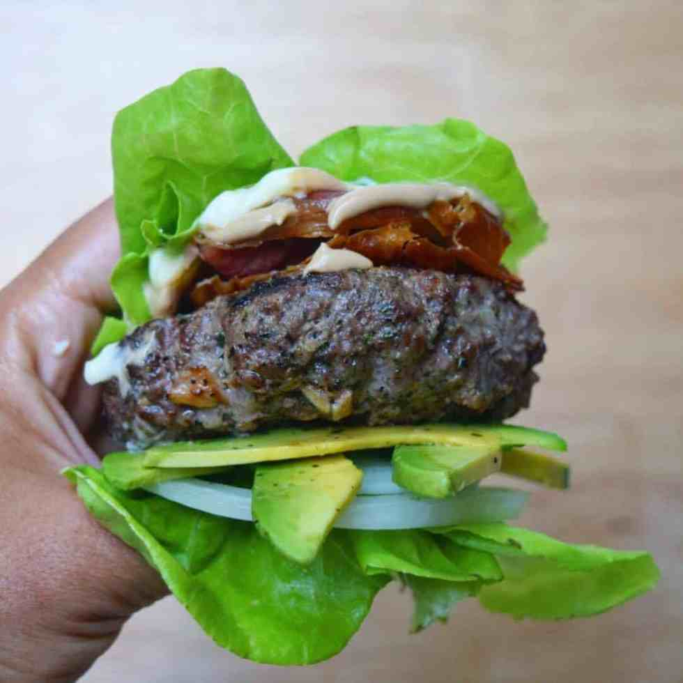 hand holding a lettuce-wrapped burger with avocado and onion