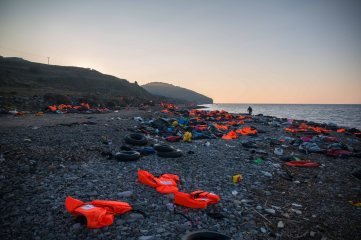 Scouring the shore strewn with life jackets