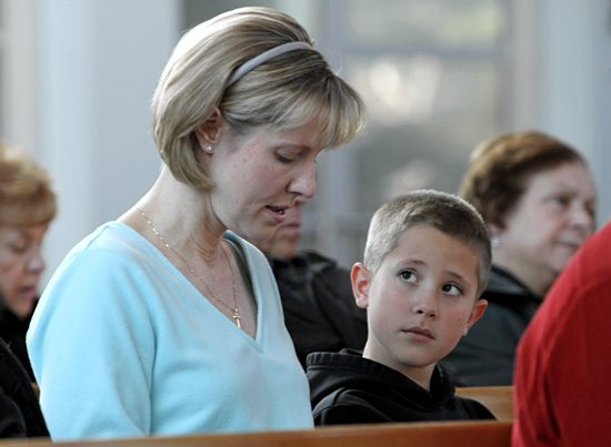 Brad Stankiewicz, 8, looks at his mother, Kathy, as she prays during a special Mass at Holy Cross Church in Nesconset, N.Y., Dec. 28 for the 26 students and staff members killed two weeks earlier at Sandy Hook Elementary School in Newtown, Conn. The Mass coincided with the feast of the Holy Innocents. CNS photo / Gregory A. Shemitz