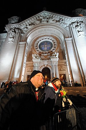 On the steps of the Cathedral of St. Paul, Father Erich Rutten, director of campus ministry at the University of St. Thomas in St. Paul, watches the final race of the Red Bull Crashed Ice World Championship. Nearly 80,000 people crowded around the Cathedral of St. Paul Jan. 26 to watch the event. Last year's champion, Canadian Kyle Croxall, was victorious again, beating his brother Scott and American Cameron Naasz in the final round. (Dianne Towalski/The Catholic Spirit)