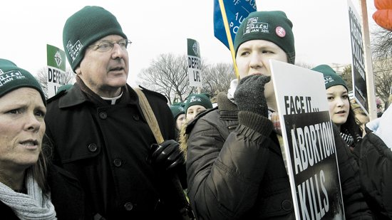 Archbishop John Nienstedt stands with Nancy Schulte Palacheck, left, and Genevieve McCarthy, then a senior at Providence Academy in Plymouth, during a rally on the National Mall in Washington, D.C. in this 2011 file photo. Archbishop Nienstedt will again join a group of students from the archdiocese participating in the rally and March for Life. Jan. 25. File photo by Maria Wiering Pedersen