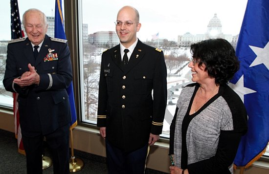 Father Michael Creagan, center, receives applause from his uncle, retired Gen. Robert Reed, left, and his mother, Judy Green, following his official commissioning Feb. 28 as a Minnesota Army National Guard Chaplain. Gen. Reed came to the Twin Cities from his home in South Carolina to conduct the swearing in. Green belongs to St. Michael in Stillwater, a parish where Father Creagan has served. He now is the pastor of St. Joseph in West St. Paul. (Dave Hrbacek / The Catholic Spirit)