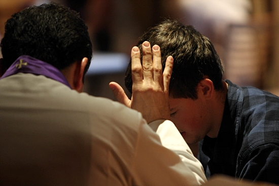 A priest hears a young man's confession in this file photo. CNS photo / Gregory A. Shemitz