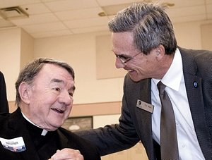 Msgr. Jerome Boxleitner, left, talks with Catholic Charities CEO Tim Marx at the Dorothy Day Center Community Breakfast last May in St. Paul. (Photo courtesy of Catholic Charities)