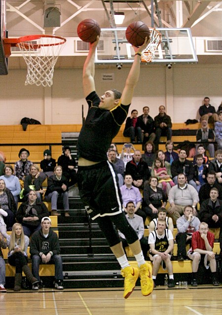 DeLaSalle High School junior Travis Reid tries to dunk two basketballs at once during a slam dunk contest that took place between games. It featured players from local high Catholic high schools, including Reid's teammate, sophomore Jarvis Johnson, who won the competition. In addition to successfully dunking the two balls, Reid also did a dunk in which he jumped over three boys crouched under the hoop. (Dave Hrbacek/The Catholic Spirit)