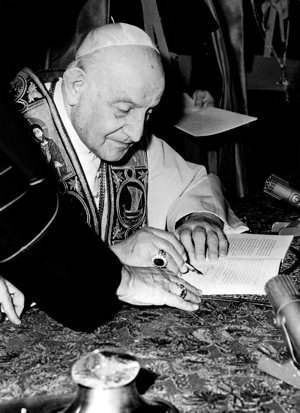 "Pope John XXIII signs his encyclical ""Pacem in Terris"" (""Peace on Earth"") at the Vatican in this 1963 file photo.  CNS photo"