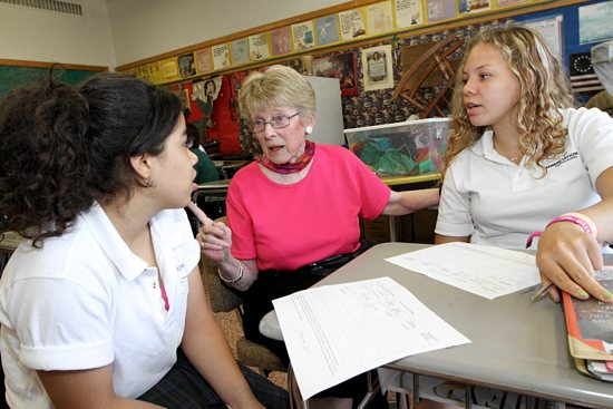 Teacher Marie Murphy, center, helps seventh-graders Maria Clubb, left, and Kalia Quirk with social studies at Annunciation School in Minneapolis May 20. Murphy, who has taught at the school for 48 years, is retiring at the end of the school year, which is June 7. Dave Hrbacek / The Catholic Spirit