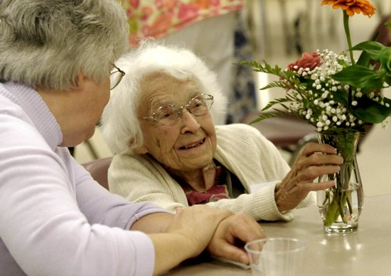 Phoebe Nosker, 98, talks with Dorothy Berghoff about the flowers on the table during a brunch July 27 at St. Bridget in Minneapolis to honor active members of the parish over 90 years old. Dianne Towalski / The Catholic Spirit