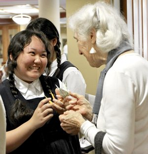 A choir member from Japan shares a smile with a member of the Carondelet Village in St. Paul. After their performance, the girls gave handmade origami to each of the audience members. Caroline Rode/The Catholic Spirit