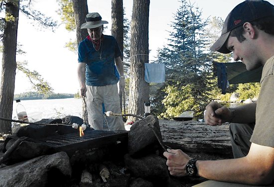 Colin Jones, right, of St. John Vianney College Seminary in St. Paul roasts marshmallows with Archbishop John Nienstedt during a recent trip to Minnesota's Boundary Waters. Photo courtesy of Archbishop Nienstedt