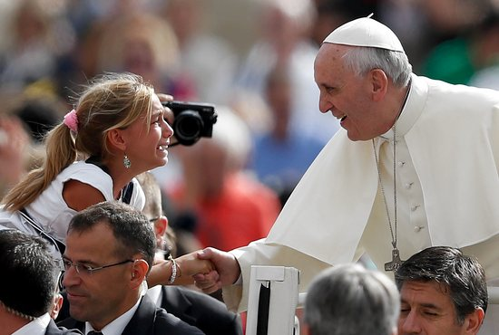 Pope Francis shakes hands with a girl as he arrives to lead his general audience in St. Peter's Square at the Vatican Sept. 11. CNS photo/Paul Haring