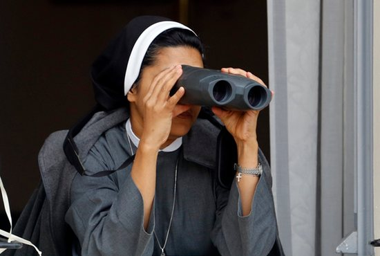 POPE WATCHING: A nun looks through binoculars as Pope Francis arrives to celebrate Mass outside the Basilica of St. Francis in Assisi, Italy, Oct. 4. CNS photo/Stefano Rellandini, Reuters