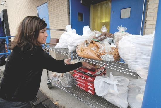 Volunteer Susie Van Hoomissen, a member of St. Patrick in Edina, loads food onto a cart at Sharing and Caring Hands in Minneapolis. Dianne Towalski / The Catholic Spirit
