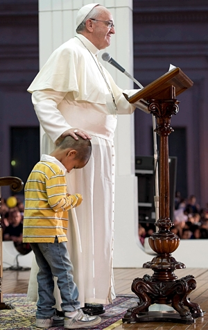 Pope Francis touches the head of a child as he addresses pilgrims in St. Peter's Square at the Vatican Oct. 26. He addressed an estimated 100,000 people taking part in a Year of Faith celebration of family life.  CNS photo/L'Osservatore Romano via Reuters