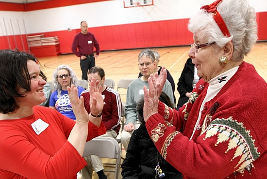 Donna Heins, right, gives a high five to Melissa, a participant in the faith formation program for adults with special needs at St. Odilia in Shoreview. Dave Hrbacek / The Catholic Spirit