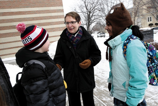 Holy Spirit School Principal Mary Adrian, center, talks with fifth-grader Sam McTeague, left, and sixth-grader Kate Dario after school. On most days, Adrian stands outside the building both before and after school so she can take advantage of the opportunity to visit with students.  Dave Hrbacek/The Catholic Spirit