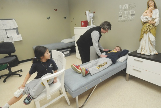 Retired registered nurse Janice Donais checks on first-grade student Andy Olson, while Izzy Yang, also in first grade, looks on in the nurse's office at St. Stephen School in Anoka Jan. 24. Donais coordinates a group of volunteers with health care backgrounds to staff the office. Dianne Towalski / The Catholic Spirit
