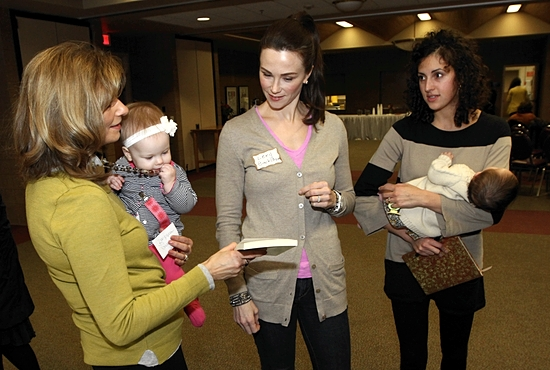 From left, Jeannine Backstrom of St. Albert in Albertville, her daughther-in-law Lexy Backstrom of St. Louis King of France in St. Paul, and Stephanie Stokman of Nativity of Our Lord in St. Paul check out a book at The Well-Read Mom conference Jan. 10 at St. John the Baptist in New Brighton. Dave Hrbacek/The Catholic Spirit