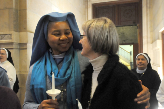 Immaculate Heart of Mary Sister Maria Chinweze Enujiofor hugs Visitation Sister Karen Mohan as they gathered for a blessing of candles.
