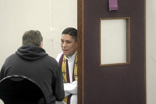 Father Humberto Palomino, pastor of St. Mark in St. Paul, hears confession during the breakfast break.