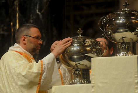 Deacon Paul Tschann places a vessel of oil on a pedestal during the Mass. Deacon Tom Michaud Jr. is behind the oils.