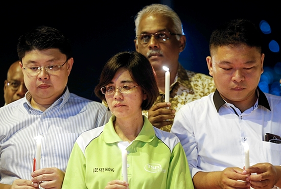 CANDLELIGHT VIGIL People hold candles during an April 7 candlelight vigil for passengers onboard the missing Malaysia Airlines Flight MH370, in Kuala Lumpur, Malaysia. CNS photo/Samsul Said, Reuters