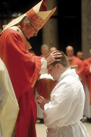John Powers kneels before Archbishop John Nienstedt for the laying on of hands.