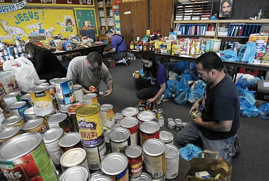 Volunteers Erwin Radoc, right, his daughter Ana, 12, and Tim Koran help organize the food that was delivered.