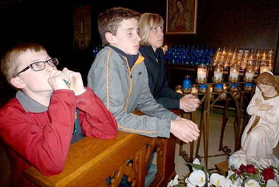 SPECIAL PILGRIMAGE  Brian Meyer, left, and Sam Nelson, both 7th-graders at Notre Dame Academy in Minnetonka, and Sam's mom Kris Nelson, right,  prayed in the crypt at the Shrine of Our Lady of Good Help in New Franken, Wisc., near Green Bay. The 7th-grade class visited the shrine April 29 and 30. Before they left, they gathered the prayers of their church and school communities and prayed them at the hallowed site seeking the intercession of the Blessed Virgin Mary. Photo courtesy of Jeanne Sharp