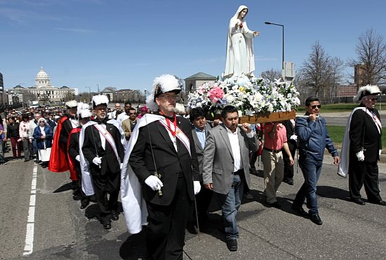 Flanked by members of the Knights of Columbus, parishioners from Our Lady of Guadalupe in St. Paul carry a statue of Mary as they march down John Ireland Boulevard on their way to the Cathedral of St. Paul during the 67th annual Archdiocesan Family Rosary Procession May 4. The event, which started at the State Capitol, featured parts of the rosary in Spanish. Dave Hrbacek/The Catholic Spirit
