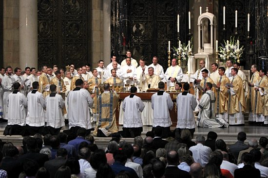 Priests and bishops, including the newly ordained, gather around the altar as Archbishop John Nienstedt delivers the prayer of consecration during the priest ordination Mass May 31 at the Cathedral of St. Paul. All priests in attendance were invited to come forward into the sanctuary during the eucharistic prayer.