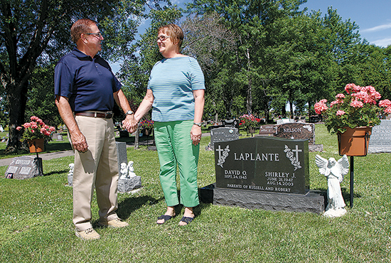 Dave and Kathy LaPlante stand at the spot where they first made a love connection — the St. Vincent de Paul parish cemetery in Brooklyn Park, where their respective deceased spouses are buried just two plots apart.  Dave Hrbacek/The Catholic Spirit