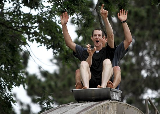 Father Nick VanDenBroeke gets ready to go down a giant waterslide with a fellow priest, Father Paul Shovelain, during Extreme Faith Camp at Big Sandy Lake June 25. Dave Hrbacek/The Catholic Spirit