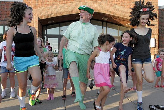 Father Paul Jarvis, center, goes green July 26 during the festival for his parish, St. Joseph in Rosemount, as he does an Irish jig with a group of children. The festival coincided with Rosemount Leprechaun Days.  Dave Hrbacek/The Catholic Spirit