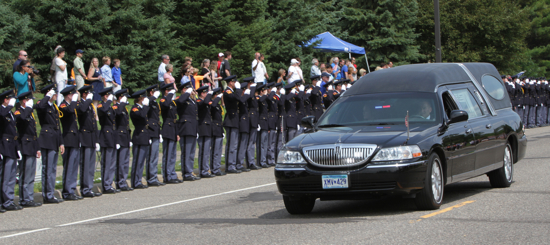 St. Thomas Academy Cadets line up and salute as the hearse containing the body of Officer Scott Patrick passes by the Mendota Heights School Aug. 6 following the funeral. An earlier procession featured law enforcement officers and vehicles from around Minnesota, plus a few from Wisconsin. Although Officer Patrick was not Catholic, he was considered a friend of the school, and was a frequent visitor. Two of his fellow officers on the Mendota Heights police force are alums of the school, Sgt. Brian Convery and Officer Bobby Lambert. Officer Patrick was shot and killed during a traffic stop July 30.