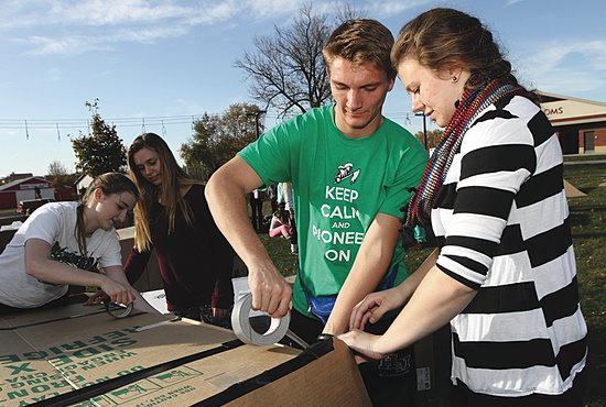 CARDBOARD CITY Alaina Anderson, right, and Nick Nelson, seniors at Hill-Murray School in Maplewood, construct a cardboard box dwelling as part of an event Oct. 16 and 17 at the Minnesota State Fairgrounds to create awareness and raise money for the homeless. The two, who are co-presidents of the student group Sowers of Justice, led a group of more than 50 Hill-Murray students that slept overnight in the boxes. Also participating were sophomores Emily Schabert, left, and Sydney Polski. Proceeds from the event, called Cardboard Box City, went to a local organization called Project Home and Families Moving Forward. Hill-Murray students raised $700 and also led a prayer service at the event. Dave Hrbacek/The Catholic Spirit