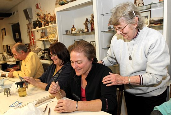Benedictine Sister Virginia Matter, right, watches Barb Marohnic work on a pottery project during class Oct. 20 at St. Paul's Monastery in Maplewood. Also taking part in the class are Dennis Cavanaugh, left, and Debbie Wermager. Dave Hrbacek/The Catholic Spirit